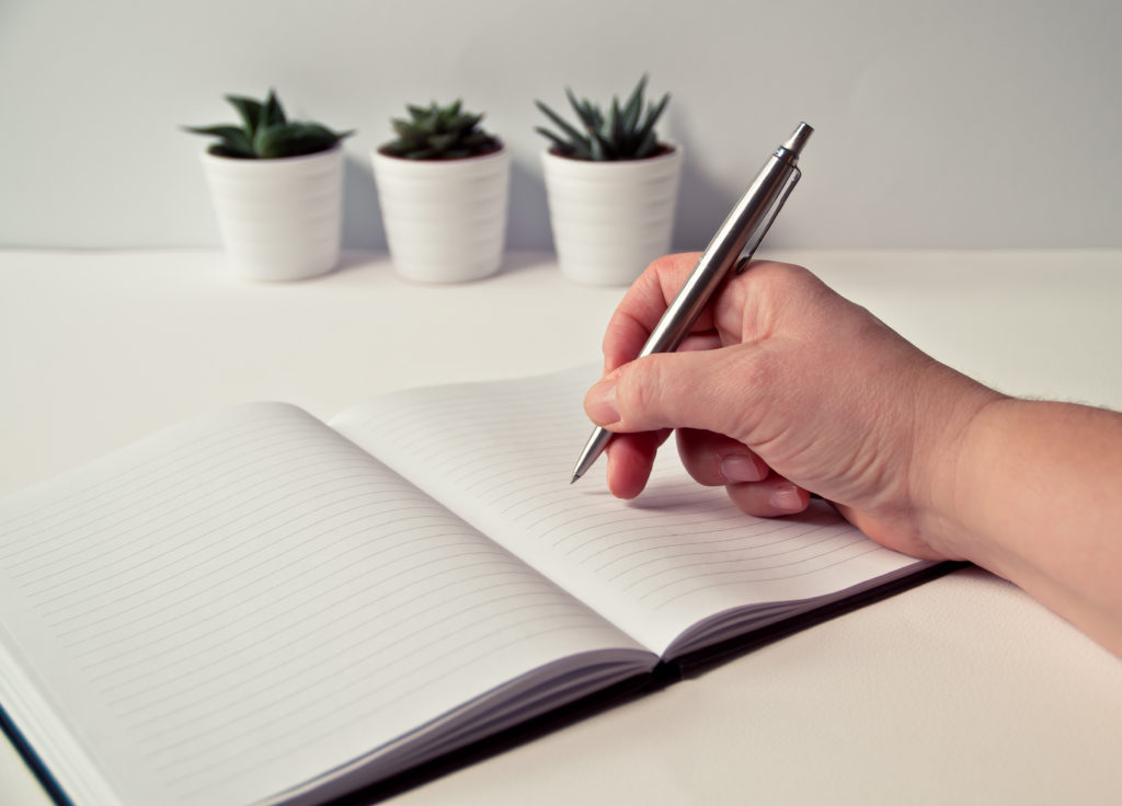 A hand holding a pen on a notepad to signify writing SEO content.